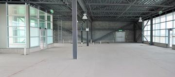 有钢粱、玻璃窗和混凝土墙的空的仓库 免版税库存图片