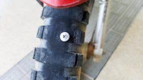 有钢螺丝的特写镜头摩托车泄了气的轮胎 免版税库存图片