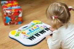有钢琴玩具的女孩 免版税库存图片