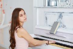 有钢琴的画象美丽的女孩 库存照片