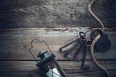 有钥匙、葡萄酒灯、瓶和绳索的老生锈的锁 免版税图库摄影