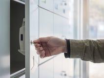 有钥匙开放衣物柜的手在更衣室 免版税库存图片