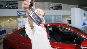 有钥匙的一名年轻回教妇女从一辆新的汽车 影视素材