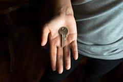 有钥匙的女性手在棕榈 免版税库存照片