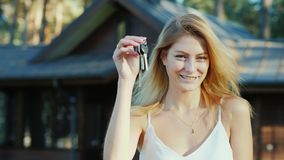 有钥匙的年轻女人从家 微笑,看照相机 新的木村庄在背景中 影视素材