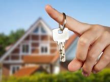 有钥匙的手在房子前面 库存照片