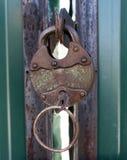 有钥匙的老生锈的金属挂锁在绿色金属给特写镜头装门 库存照片