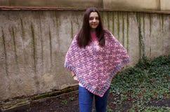 有钩针编织雨披的青少年的女孩 免版税图库摄影