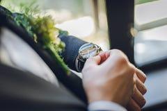 有钮扣眼上插的花和时钟的新郎 新郎在时钟waching 美好的婚礼 库存照片