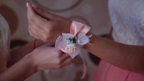 有钮扣眼上插的花的女傧相新娘在他的手上 股票录像
