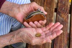 有钱包和硬币的一个老妇人 库存图片