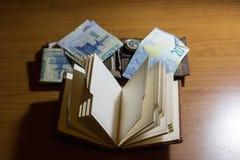 有钱包和金钱的空的笔记本在书桌上的边 库存图片