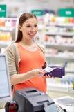有钱包的孕妇在钱柜在药房 免版税库存照片