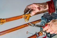 有钳子的滤水器和锁匠手 免版税库存图片
