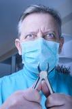 有钳子的疯狂的牙医在他的手上 免版税库存图片