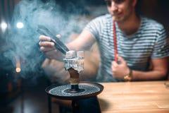 有钳子的年轻人点燃煤炭在水烟筒酒吧 图库摄影