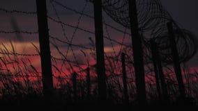 有铁丝网和草的篱芭在多云红蓝色天空的背景 影视素材