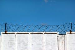 有铁丝网的白色具体篱芭反对蓝天 库存图片
