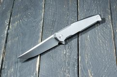 有铁夹子和发光的刀片的刀子 黑色背景 库存照片