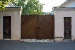 有铁把柄的老木入口门 在其中每一边的两个另外的小输入木门 第18个c的建筑学 库存图片