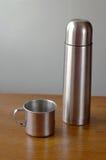 有铁的热水瓶杯子在桌上 免版税库存图片