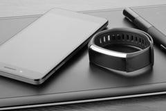 有铁笔、智能手机和活动跟踪仪的数字式艺术委员会图形输入板黑暗的木表面上 工作场所细节  库存照片