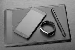 有铁笔、智能手机和活动跟踪仪的数字式艺术委员会图形输入板黑暗的木表面上 工作场所细节  Mo 免版税库存照片
