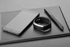 有铁笔、智能手机和活动跟踪仪的数字式艺术委员会图形输入板黑暗的木表面上 工作场所细节  Mo 免版税库存图片