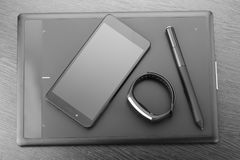 有铁笔、智能手机和活动跟踪仪的数字式艺术委员会图形输入板黑暗的木表面上 顶视图 wor细节  免版税库存照片