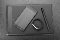 有铁笔、智能手机和活动跟踪仪的数字式艺术委员会图形输入板黑暗的木表面上 顶视图 wor细节  图库摄影