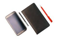 有铁笔笔的一个智能手机和有红色笔的一个黑笔记本 免版税库存照片