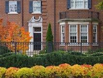 有铁篱芭的大砖房子 免版税库存照片