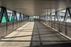 有铁路轨的空的天桥桥梁走道和钢屋顶连接到天空火车站 免版税库存照片