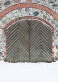 有铁铆钉的老木门在wi的花岗岩墙壁 图库摄影