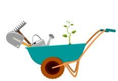 有铁锹、犁耙、一把喷壶和新芽的独轮车 图库摄影