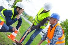 有铁锹的小组工作者开掘沟槽的 免版税库存照片