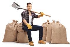 有铁锹的快乐的年轻农夫坐粗麻布大袋 免版税库存照片