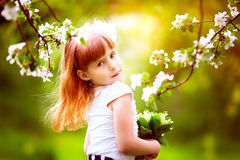 有铃兰花束的愉快的小女孩有的 免版税库存照片