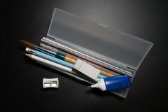 有铅笔、笔、橡皮擦、磨削器和油漆刷的基本的白色塑料铅笔盒在黑背景 库存图片