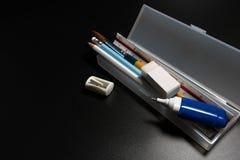 有铅笔、笔、橡皮擦、磨削器和油漆刷的基本的白色塑料铅笔盒在黑背景 图库摄影