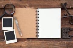 有铅笔、钥匙和放大镜的空白的笔记本 免版税库存照片