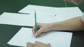 有铅笔凹道的人的手在白色桌背景的纸穿戴 影视素材