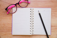 有铅笔和镜片的空白的笔记本 库存照片