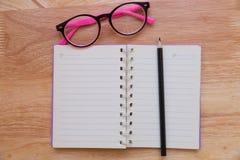 有铅笔和镜片的空白的笔记本 免版税库存照片