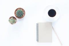 有铅笔咖啡杯和仙人掌的笔记本在白色 免版税库存照片