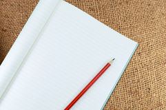 有铅笔孤立的笔记本在棕色麻袋布,葡萄酒米黄织品纹理背景 免版税库存图片