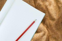 有铅笔孤立的笔记本在棕色麻袋布,葡萄酒米黄织品纹理背景 库存图片