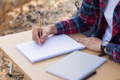有铅笔文字的女性手在笔记本 免版税库存图片