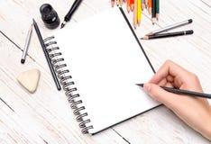 有铅笔的人的手在笔记本画 免版税库存照片