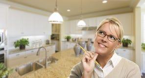 有铅笔的作白日梦的妇女在美丽的厨房里面 库存图片